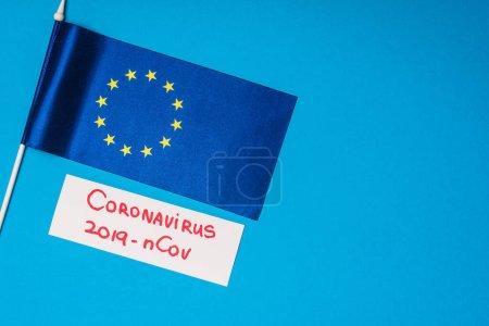 Photo pour Vue du dessus du drapeau de l'unité européenne et carte avec coronavirus 2019-nCov lettrage sur fond bleu - image libre de droit