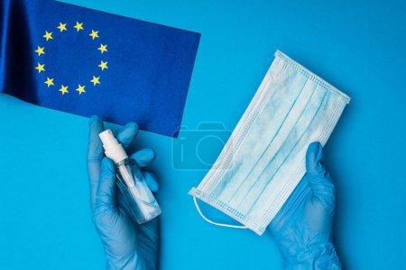 Photo pour Vue du dessus du médecin tenant un masque médical et une bouteille de désinfectant pour les mains près du drapeau de l'unité européenne sur fond bleu - image libre de droit