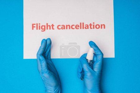 Photo pour Vue du dessus du médecin tenant une bouteille de désinfectant pour les mains près de la carte avec inscription d'annulation de vol sur fond bleu - image libre de droit