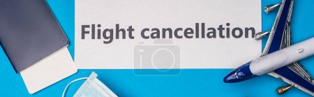 Photo for Top view of card with flight cancellation lettering near toy airplane, medical mask and passport with air ticket on blue surface, panoramic shot - Royalty Free Image