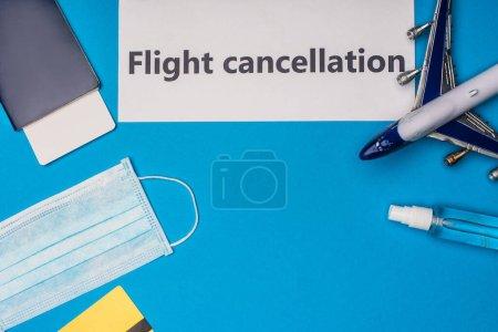 Photo pour Vue du dessus de la carte avec lettrage d'annulation de vol près du masque médical, avion jouet, passeport et billet d'avion sur fond bleu - image libre de droit