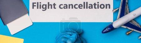Photo pour Vue du dessus du médecin près de l'avion jouet, carte avec lettrage d'annulation de vol et passeport avec billet d'avion sur la surface bleue, vue panoramique - image libre de droit