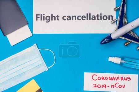 Photo pour Vue du dessus des cartes avec annulation de vol et coronavirus 2019-nCov lettrage près masque médical, carte de crédit et avion jouet sur la surface bleue - image libre de droit