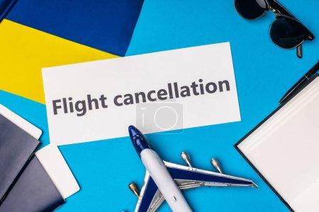 Photo pour Vue du dessus de la carte avec annulation de vol près de l'avion jouet, drapeau de l'ukraine et passeports sur fond bleu - image libre de droit