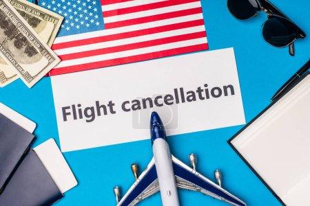 Photo pour Vue du dessus de la carte avec lettrage d'annulation de vol près de l'avion jouet, dollars et drapeau de l'Amérique sur fond bleu - image libre de droit