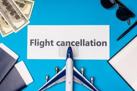 Photo pour Vue du dessus de l'avion jouet près de la carte avec lettrage d'annulation de vol, passeports et billets en dollars sur la surface bleue - image libre de droit
