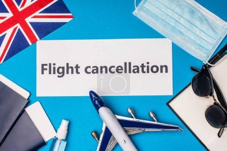 Photo pour Vue du dessus de la carte avec lettrage d'annulation de vol près du drapeau du Royaume-Uni, avion jouet et masque médical sur la surface bleue - image libre de droit
