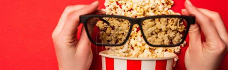 Photo for Top view of woman holding sunglasses near bucket with popcorn on red background, panoramic shot - Royalty Free Image