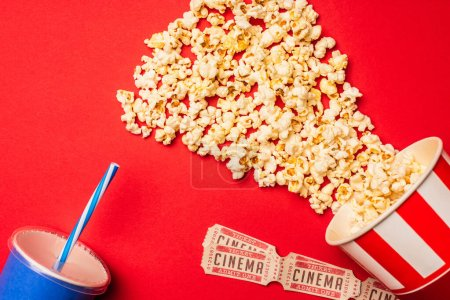 Photo for Top view of popcorn, cinema tickets and paper cup on red surface - Royalty Free Image