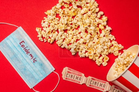 Draufsicht auf medizinische Maske mit Epidemie-Schriftzug, Popcorn und Kinokarten auf rotem Hintergrund