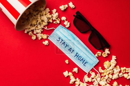 Photo for Top view of medical mask with stay at home lettering near sunglasses and popcorn on red background - Royalty Free Image