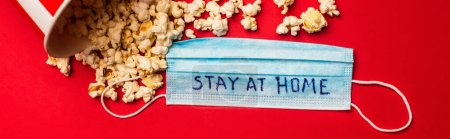 Top view of medical mask with stay at home lettering and popcorn on red surface, panoramic shot