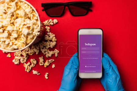 Photo for KYIV, UKRAINE - MARCH 26, 2020: Top view of person holding smartphone with instagram app near popcorn and sunglasses on red background - Royalty Free Image