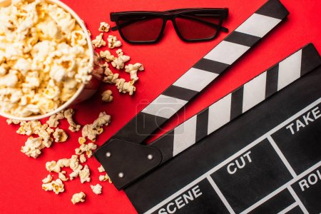 Photo for Top view of clapperboard near bucket with popcorn ans sunglasses on red background - Royalty Free Image
