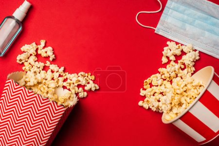 Top view of hand sanitizer, medical mask and buckets with popcorn on red surface