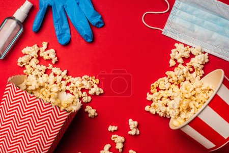 Top view of latex glove near medical mask, popcorn and hand sanitizer on red background