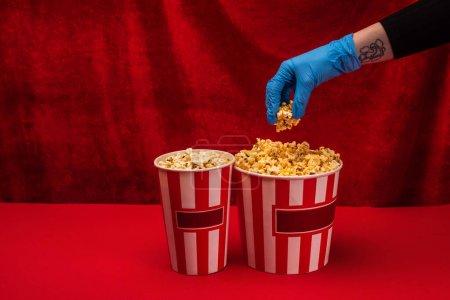 Photo pour Vue recadrée de la femme en gant de latex tenant du pop-corn sur une surface rouge avec du velours à l'arrière-plan - image libre de droit