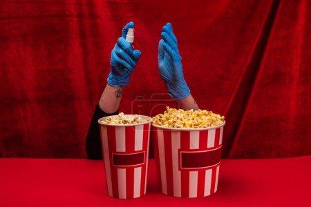 Photo pour Vue recadrée de la femme en gants de latex tenant une bouteille de désinfectant pour les mains près du maïs soufflé sur une surface rouge avec du velours à l'arrière-plan - image libre de droit