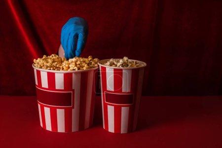 Photo pour Vue recadrée de la femme en gant de latex prenant du pop-corn du seau sur la surface rouge et du velours à l'arrière-plan - image libre de droit