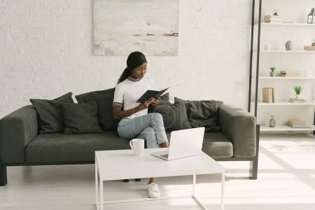 attentive african american freelancer reading notebook while sitting on sofa near table with laptop
