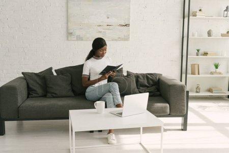 Photo pour Carnet de lecture indépendant afro-américain attentif assis sur le canapé près de la table avec ordinateur portable - image libre de droit