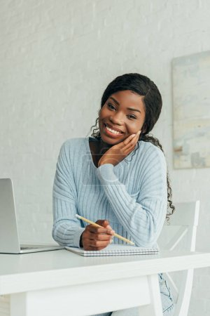 happy african american freelancer smiling at camera while holding pencil near notebook and laptop