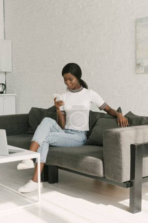Photo for Young african american freelancer chatting on smartphone while sitting near table with laptop in kitchen - Royalty Free Image