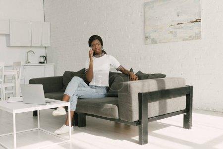 Photo pour Un freelancer africain réfléchi parle sur smartphone tout en s'asseyant sur un canapé près de la table avec ordinateur portable - image libre de droit
