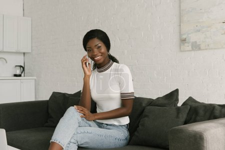 happy african american girl sitting on sofa in kitchen, talking on smartpone and smiling at camera