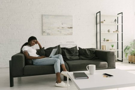 thoughtful african american freelancer sitting on sofa with laptop in spacious living room