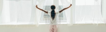 Photo for Back view of african american girl in pajamas opening window curtains in sunshine, horizontal image - Royalty Free Image