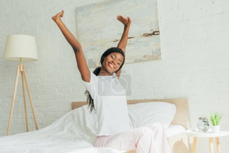 Photo for Smiling african american girl in pajamas sitting on bed with closed eyes and stretching with raised hands - Royalty Free Image