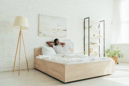 happy african american girl sitting in bed with hands behind head in spacious bedroom