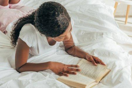 Photo pour Vue aérienne d'une jeune femme afro-américaine lisant un livre au lit - image libre de droit