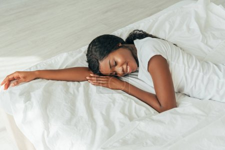 high angle view of beautiful, smiling african american girl lying on white bedding with closed eyes