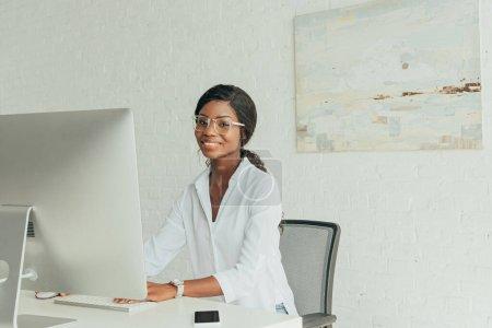 Photo pour Joyeux afro-américain freelance souriant à la caméra près de moniteur d'ordinateur à la maison - image libre de droit