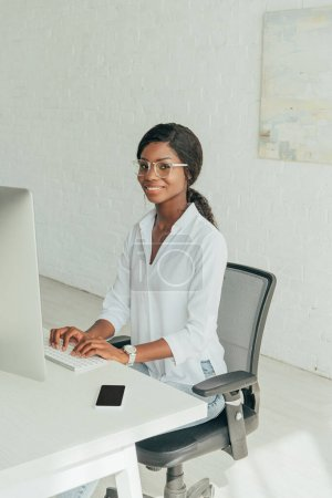 Photo pour Heureux afro-américain freelance dactylographier sur le clavier tout en souriant à la caméra - image libre de droit