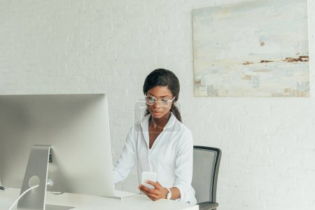 Photo for Serious african american freelancer chatting on smartphone near computer monitor at home - Royalty Free Image