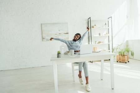 Photo for Smiling african american freelancer stretching while sitting near laptop in spacious living room - Royalty Free Image
