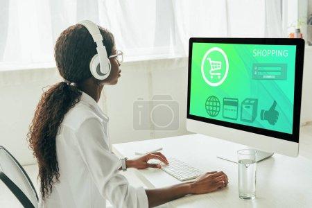 Foto de Joven freelance africano-americano en audífonos inalámbricos mirando al monitor de computadora con sitio web de compras. - Imagen libre de derechos