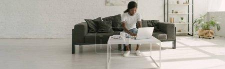 Photo pour Image horizontale d'un Africain américain travaillant sur ordinateur portable dans un grand salon - image libre de droit