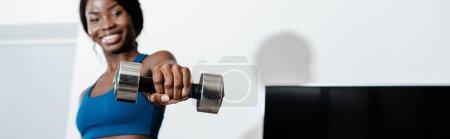 Foto de Imágenes horizontales de deportista africoamericana que sostiene campana con la mano tendida y sonriente en el salón. - Imagen libre de derechos