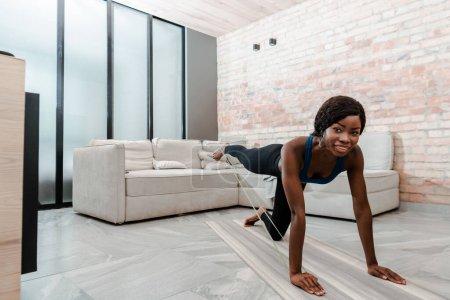 Photo pour Femme sportive afro-américaine à quatre pattes pratiquant le yoga avec bande de résistance, souriant et regardant la caméra dans le salon - image libre de droit