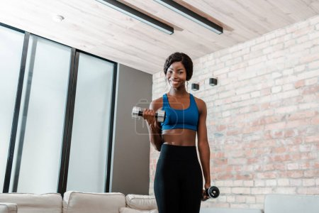 Photo for African american sportswoman smiling, training with dumbbells and looking at camera in living room - Royalty Free Image