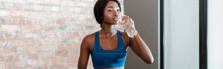 Photo for Panoramic orientation of african american sportswoman drinking water in living room - Royalty Free Image