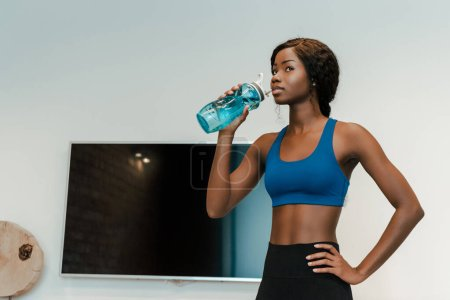 Photo for African american sportswoman with hand on hip drinking water in living room - Royalty Free Image