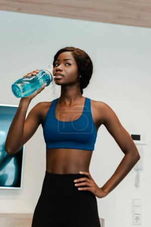 Photo for African american sportswoman with hand on hip drinking water and looking away in living room - Royalty Free Image