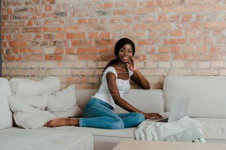Photo pour Afro-Américain pigiste à l'aide d'un ordinateur portable, souriant et regardant la caméra sur le canapé dans le salon - image libre de droit
