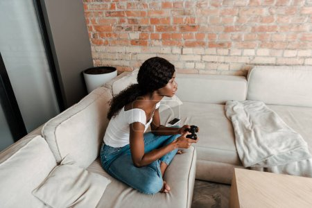 Photo for KYIV, UKRAINE  APRIL 10, 2020: high angle view of african american woman with crossed legs playing video game with joystick on sofa in living room - Royalty Free Image