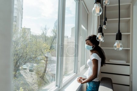 Upset african american woman in medical mask near windows in living room